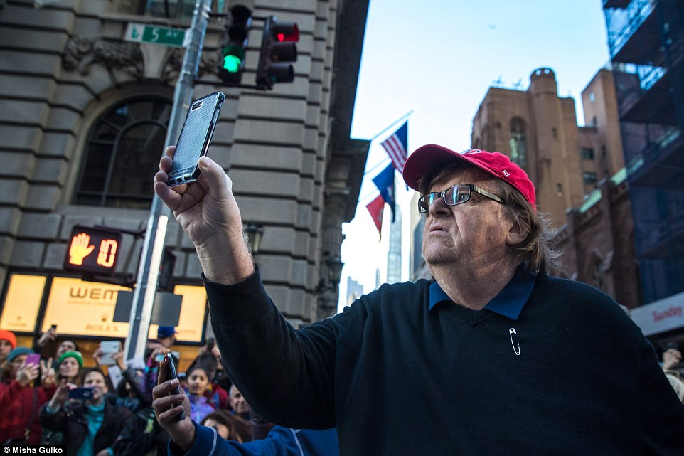 Michael Moore holds up his phone to broadcast his appearance at an anti-Donald Trump rally in New York on Saturday