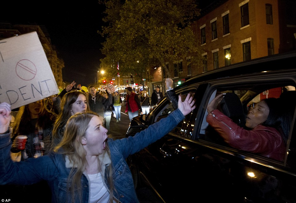 In Washington, two animated demonstrates high five as cars pass through crowds of chanting Clinton voters