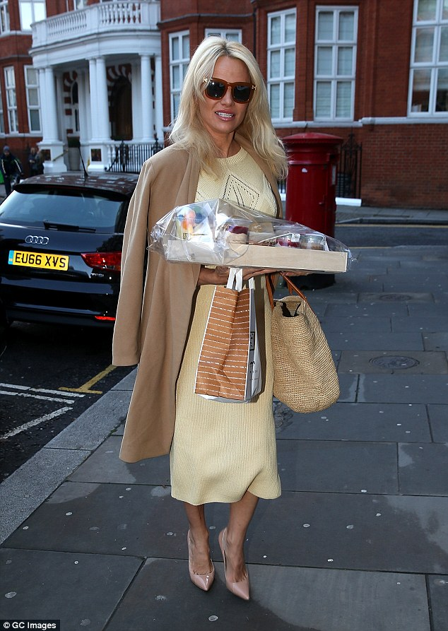 Don't drop it!The mother-of-two's arms were kept full, as she juggled a straw bag, coffee shop carrier bag and a tray laden with treats like fruit salad and vegetarian burgers