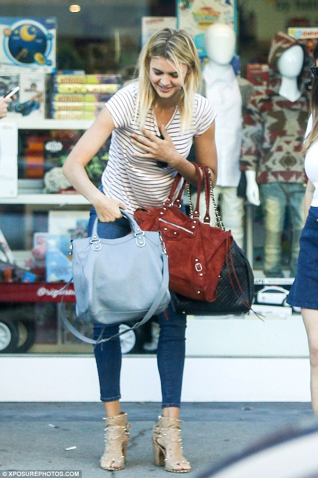 Shop til you drop them all: Baywatch Kelly Rohrbach struggled under the strain of her many bags on Saturday, as she shopped in Beverley Hills