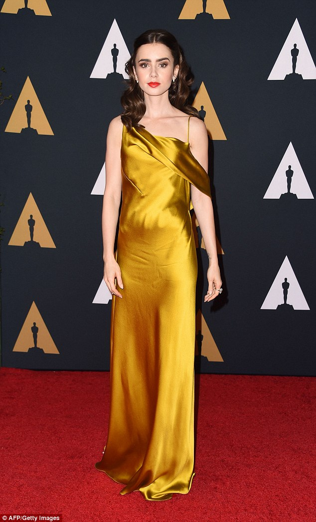 Liquid gold: Lily Collins oozed class in backless satin gown at the Academy's Governors Awards in Hollywood om Saturday night