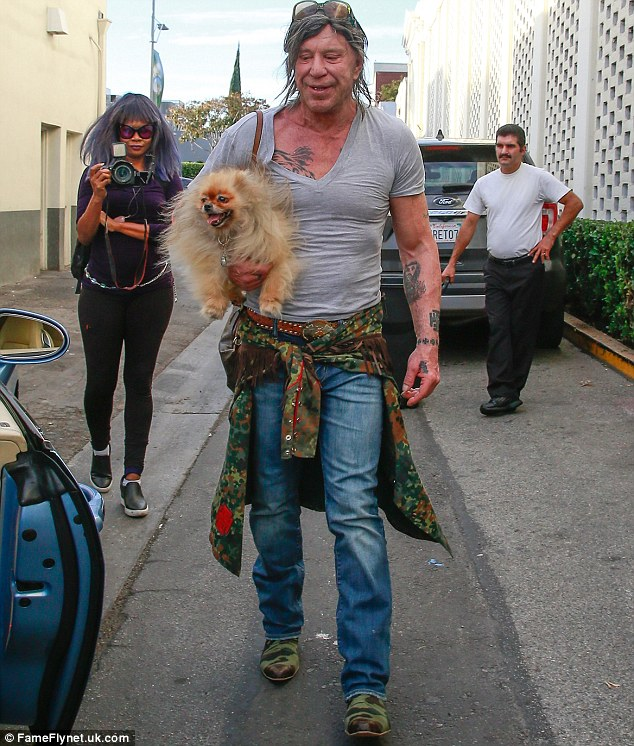 Ripped! Mickey Rourke showed he's a big softy at heart as the muscular star, 64 , cradled his beloved pooch in his arms at Cafe Roma in Beverly Hills on Saturday