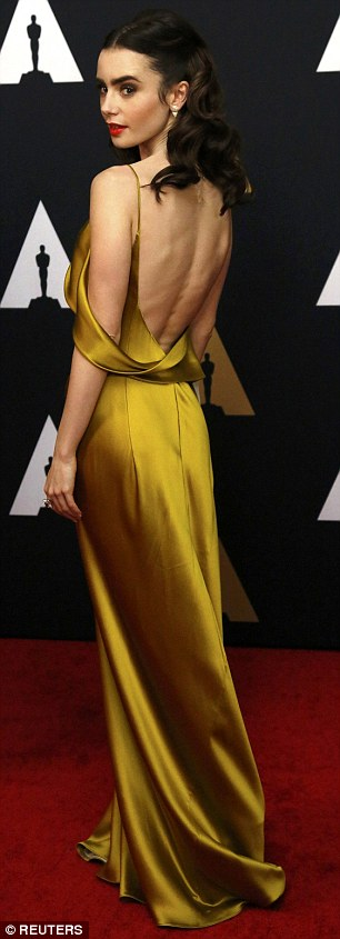 Absolutely breathtaking: Lily Collins looked like a classic movie star in her silky gold dress, which featured an asymmetrical neckline