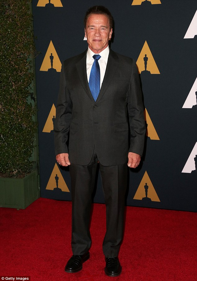 Grinning: Arnold Schwarzenegger donned a black blazer and trousers with a white button up and blue tie