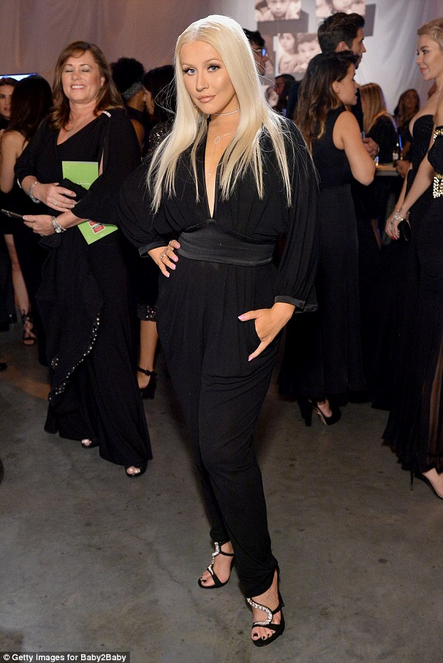 Micing it up: Songstress Christina Aguilera, 35, donned a chic, plunging black jumpsuit for the tony event