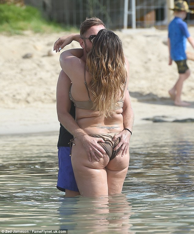Cheeky! It was clear to see he was a fan of his girlfriend's skimpy ensemble as he couldn't keep his hands off her as they packed on the PDA at the beach