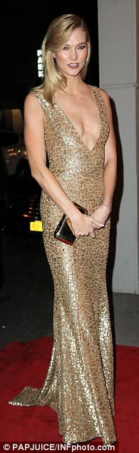 Stunning:The 24-year-old wore a gorgeous plunging gold gown that put her phenomenal figure on full display