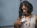 In this Thursday, Oct. 20, 2016, photo, Luincys Fernandez demonstrates how she had used the AeroForm handheld dosage controller during an interview at NewYork-Presbyterian/Columbia University Medical Center. Doctors are testing the device that would let women contribute to the breast reconstruction process at home. It is aimed at not only making treatment more comfortable and convenient, but also giving women a sense of control _ something cancer often takes away. (AP Photo/Mary Altaffer)