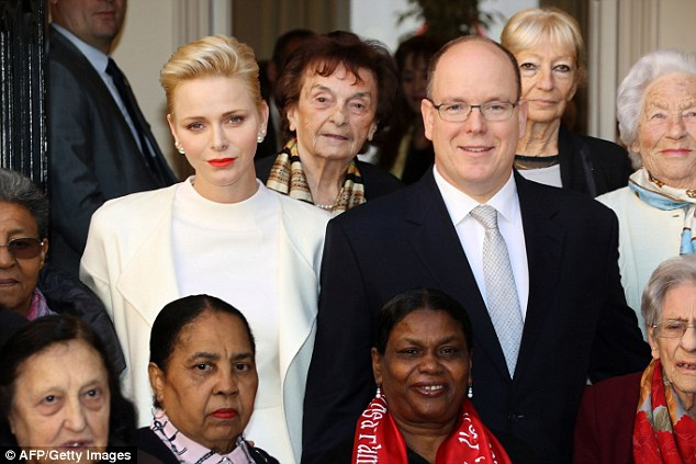 Prince Albert and Princess Charlene of Monaco pose for a family picture with refugees after giving them parcels