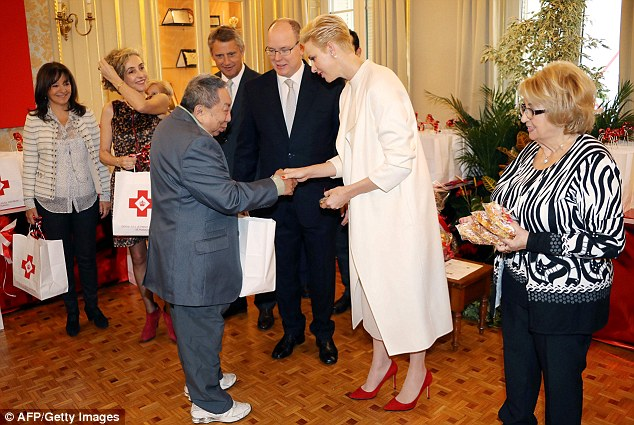 Prince Albert II (C) and Princess Charlene (C,R) of Monaco give a parcel to a Monaco's resident during the annual charity ceremony