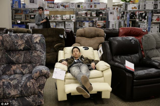 Too much to handle: A shopper naps on a recliner at Sears during Black Friday shopping at Brea Mall