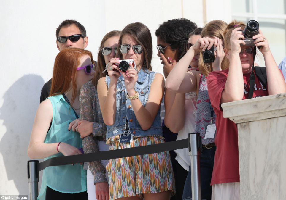 Harrymania: Supporters prepare their cameras ahead of Harry's arrival during the second day of his visit