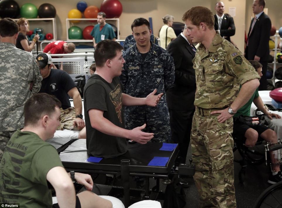 Sharing stories: Harry, pictured speaking with another wounded soldier, expressed how impressed he was with the modern technology at the center