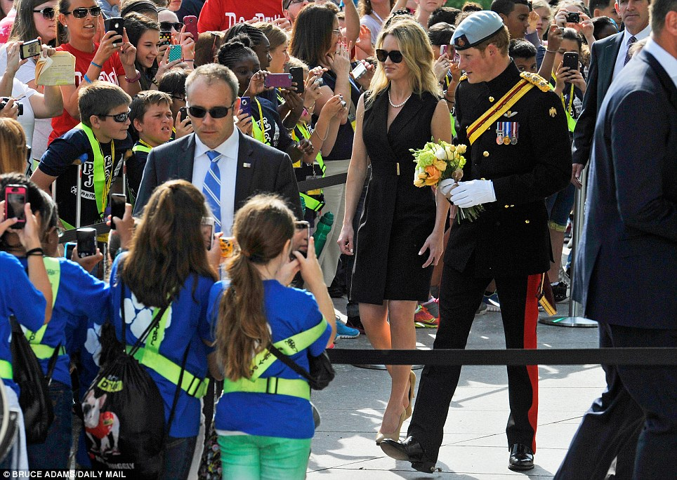 Crowds: Prince Harry lays a wreath at JFK memorial accompanied by the daughter of Patrick Hallinan the Supt. of the cemetery at Arlington National Cemetery