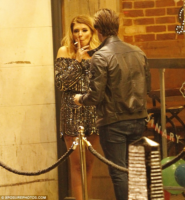 Smoking hot: Dazzling Olivia sneaked outside for a cheeky cigarette during the bash