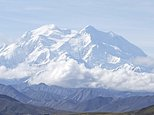 In this Aug. 26, 2016, photo, a shuttle bus carrying tourists makes its way along the park road with North America's tallest peak, Denali, in the background, in Denali National Park and Preserve, Alaska. President Barack Obama's administration in 2015 renamed the peak to its Athabascan name in a nod to Alaska Natives. As a candidate for president, Donald Trump tweeted a vow to change the mountain's name back to Mount McKinley. It's not yet clear whether Trump, now the president-elect, will act. (AP Photo/Becky Bohrer)