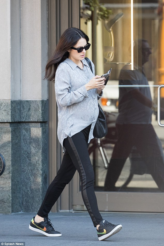 Blossoming: Dressed in a simple loose-fitting grey silk shirt, Melanie held her blossoming bump as she slipped into a pair of black leggings with a leather stripe down either side