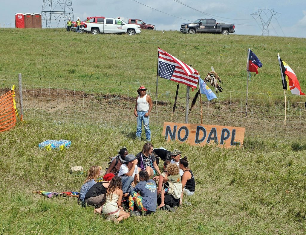Bill Left Hand, of McLaughlin, S.D., stands next to a sign at the site of a protest Friday, Aug. 12, 2016, against construction of the Dakota Access Pipeline that will cross the Missouri River in Morton County. The pipeline would start in North Dakota and pass through South Dakota and Iowa before ending in Illinois. (Tom Stromme/The Bismarck Tribune via AP)