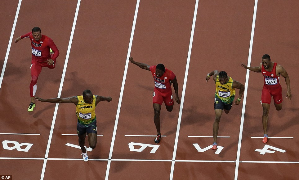 Storming in front: Bolt (second left) crosses the finish line first, ahead of fellow Jamaican Yohan Blake (second right) and bronze medallist Justin Gatlin (centre)