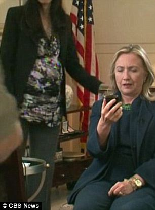 In the shadows: A then-pregnant Abedin (left in both shots) was the one to hand Clinton her Blackberry when the news came through that Muammar Gaddafi had been killed