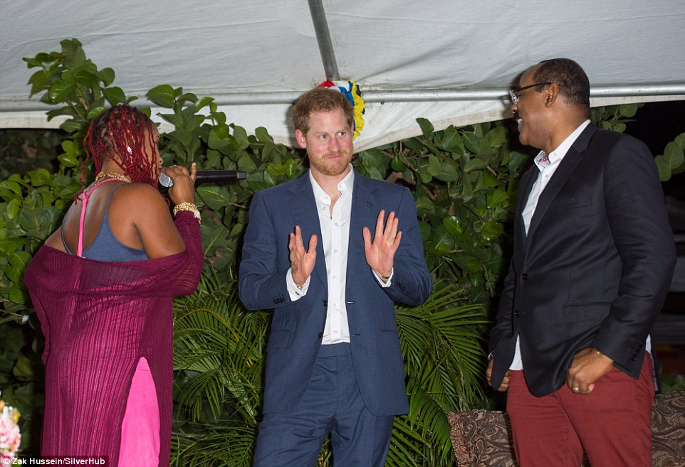 Uncomfortable: The discomfort continued as soca singer Claudette Peters (left) invited the prince to join in a special Antiguan dance - despite her sultry invitation, he didn't seem enthused