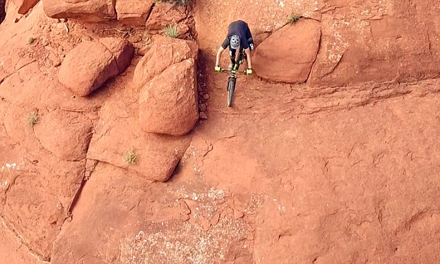 Daredevil cyclists teeter on edge of a sheer rock face in amazing drone video