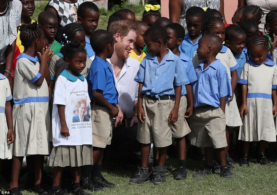 It's that t-shirt again! Prince Harry meets a gang of reception age children after taking the mangrove boat tour - and pokes his tongue out at one of them