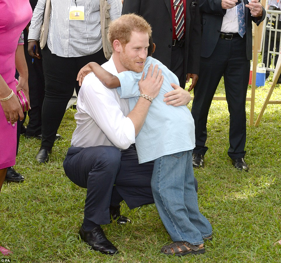 Prince Harry hugged the youngster after he attended the charity event in the tropical grounds of Government House in St John's, Antigua