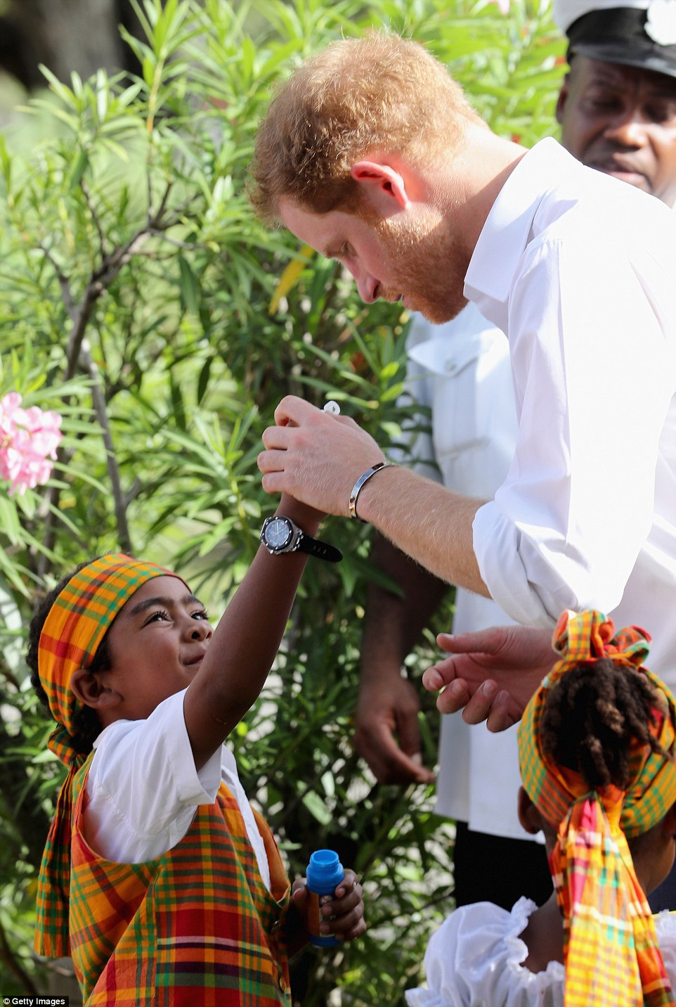 He's a big kid at heart: Prince Harry helped out a smiling child blow bubbles