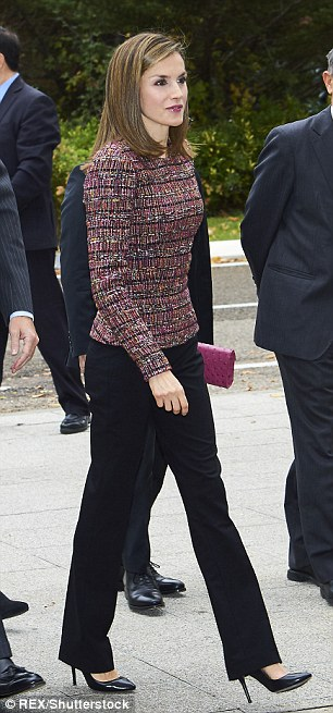The former journalist added plum coloured accents to her outfit in the form of a fitted tweed jacket and an elegant purple clutch