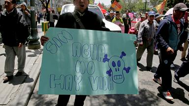 a demonstrator holds a banner during a protest in a rally against the rationing of water due to drought, in la paz