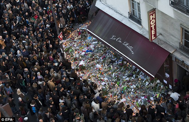 Tribute: A large crowd gathers to lay flowers and candles in front of Le Carillon, one of the bars Abdeslam is said to have driven to