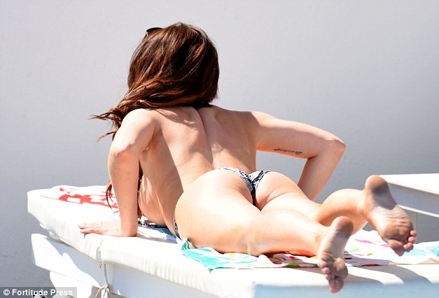 Peeling it off: Jess proved herself to be extremely body confident as she pushed up on the sunlounger