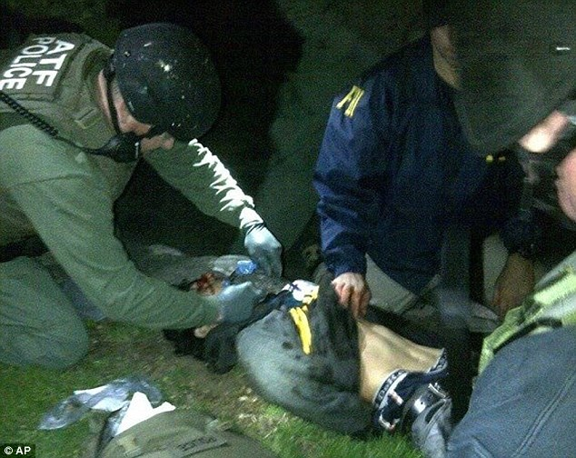 Wounded: Dzhokhar Tsarnaev, seen here moments after he was pulled from the boat where he was hiding, suffered a throat wound and a leg wound