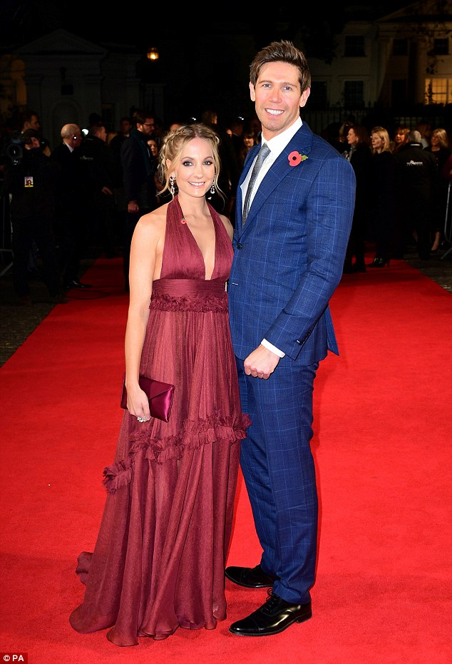 Purrfect pair: Joanne was joined by her husband James Cannon at the premiere, who looked sophisticated and suave in a navy checkered suit that complemented her gown