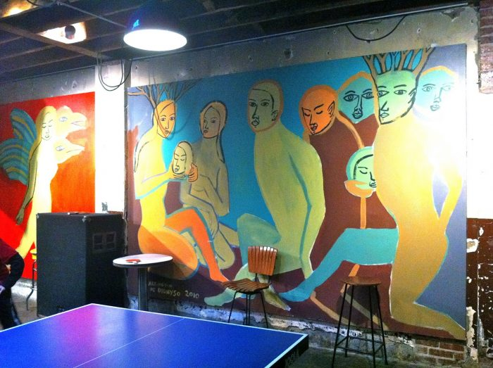 This is the mural prominently on display at Comet Ping Pong. It depicts strange people holding the heads of smaller people.
