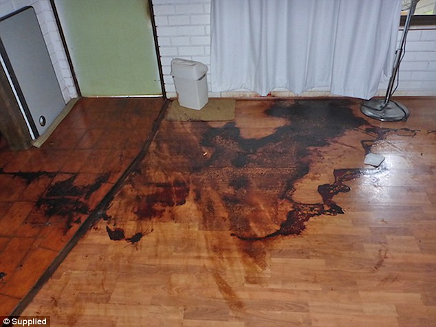Blood from a crime scene on the ground splatted across tiles and floorboards