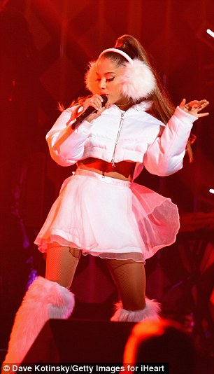 Baring her belly: The Christmas & Chill crooner wore a white lacy bra-top, matching chiffon-shelled mini-skirt, and fuzzy over-the-knee boots selected by stylist Law Roach