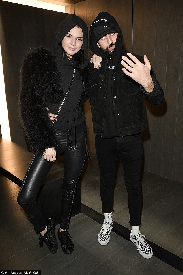 Babe in black: For her evening of party hopping, the realty star wore a pair of studded leather pants - no doubt from a yet-to-be released collection from RtA - with a black hooded jumper and a cropped fur jacket