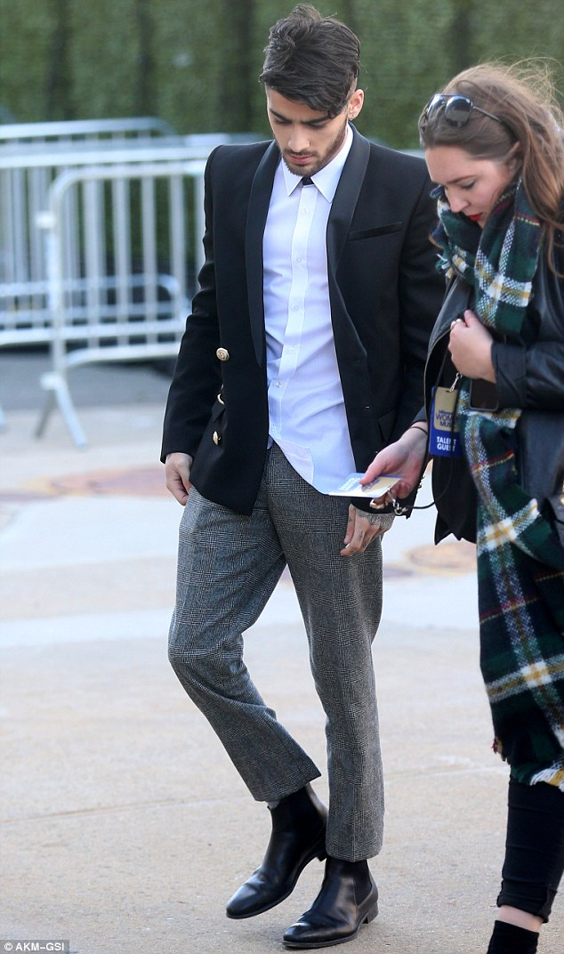 Cutting a cool figure: The singer cut a dapper figure in a black blazer and white shirt worn with grey tweed trousers and black Chelsea boots