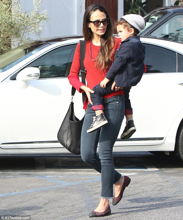 So sweet: The 36-year-old cut a stylish figure in a red blouse with skinny jeans and flats; pictured heading inside the pop up shop with son Julian