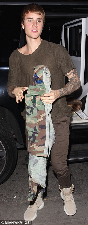 A change of heart: On a warm night in Los Angeles the hit-maker appeared to change his mind by opting to switch the heavy looking coat for a significantly lighter camouflage jacket