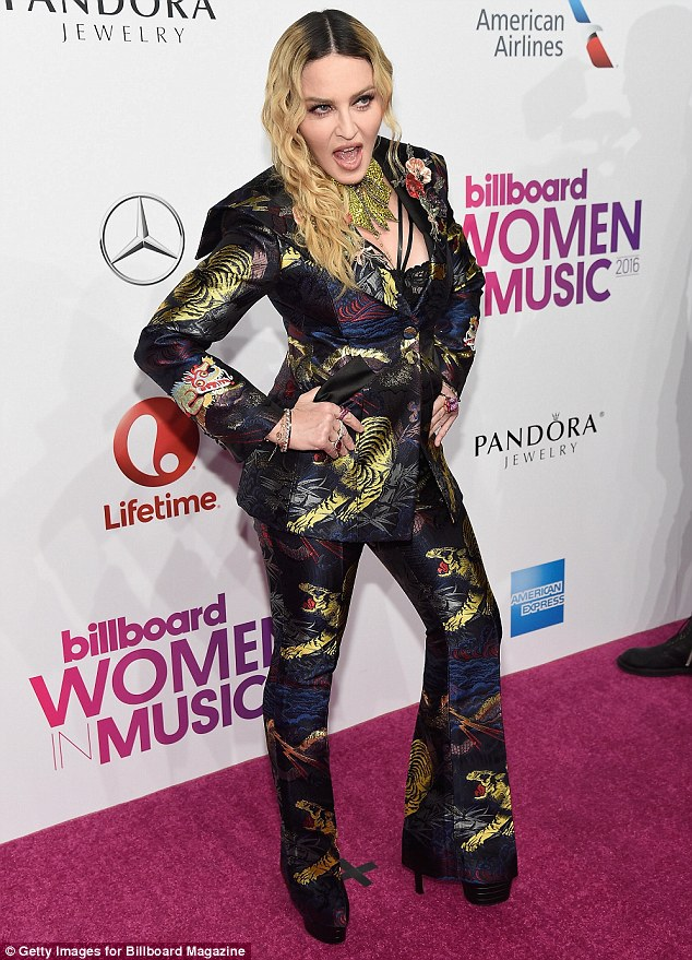 It suits her: The singer looked sharp in a Gucci trouser suit featuring gold tigers across the matching set