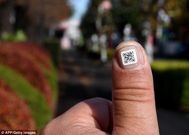 A Japanese city has introduced a novel way to keep track of senior citizens with dementia: tagging their fingers and toes with scan-able barcodes. Pictured, a city officer displays a QR code on his fingernail near the Iruma city hall in Iruma