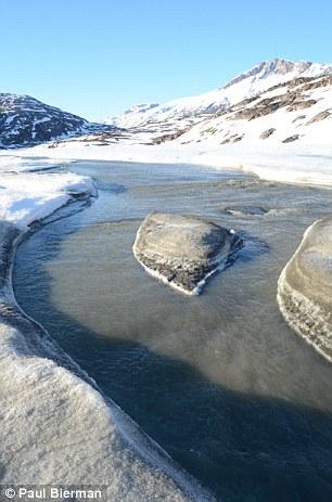 Meltwater stream carrying silt-laden run off through melting summer snow toward the East Greenland margin near Kulusuk.