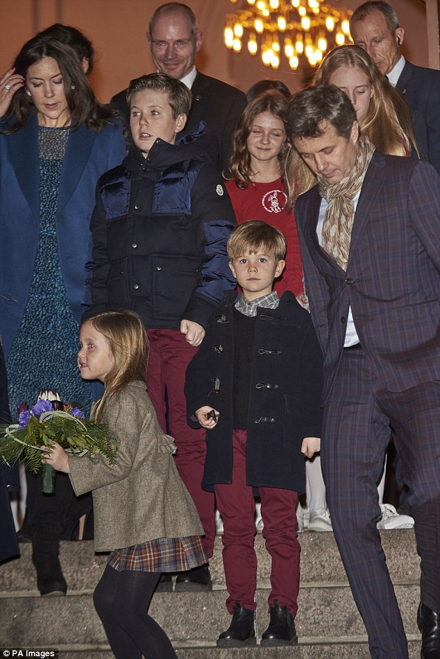 Adorable: Little Josephine looked cheeky as she carried a large bouquet of flowers, her family walking behind her