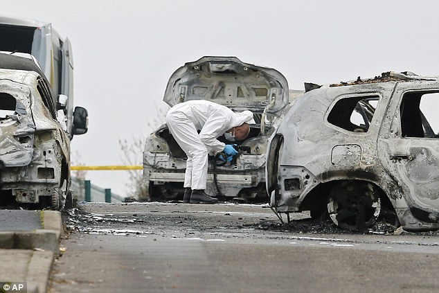 The fire gutted the car and spread to nearby vehicles but police arrived on the scene before it engulfed the van, freeing the two guards who escaped unharmed, the investigators said