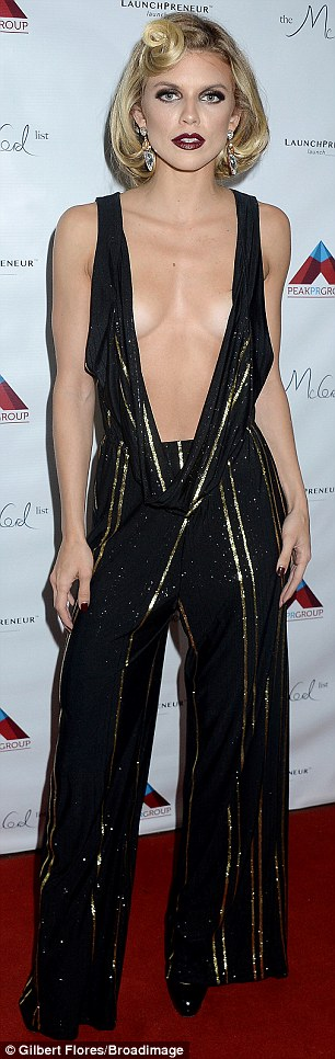 The lady is a vamp! The former model and actress looked sensational in the black jumpsuit that featured vertical shiny gold stripes and a peek-a-boo cut-out at the back