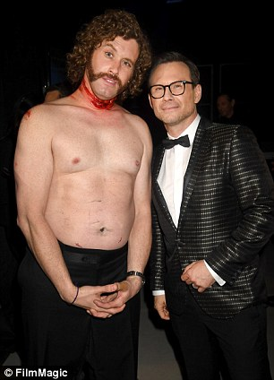 Pictured, Miller with a fake neck wound alongside actor Christian Slater on Sunday