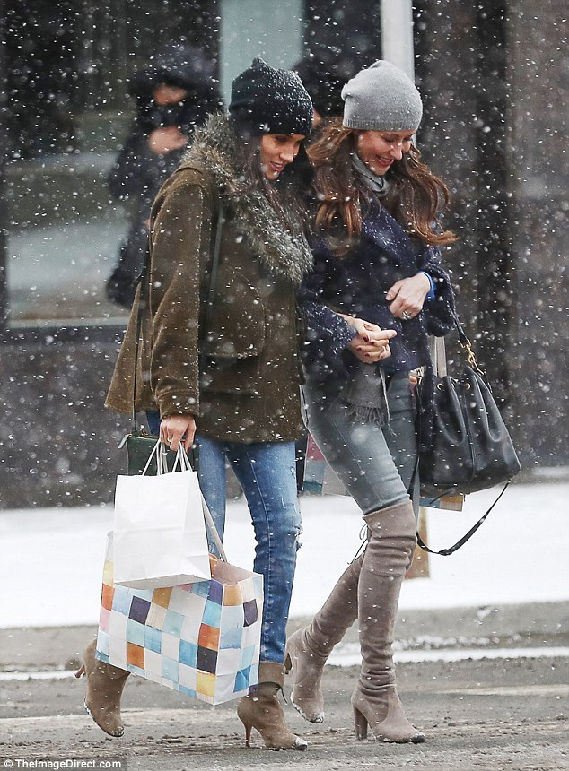 Markle and Mrs Mulroney walked arm in arm as they walked through the snow, the actress holding two shopping bags from the successful trip